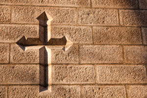 A Christian cross carved into a weathered stone wall.